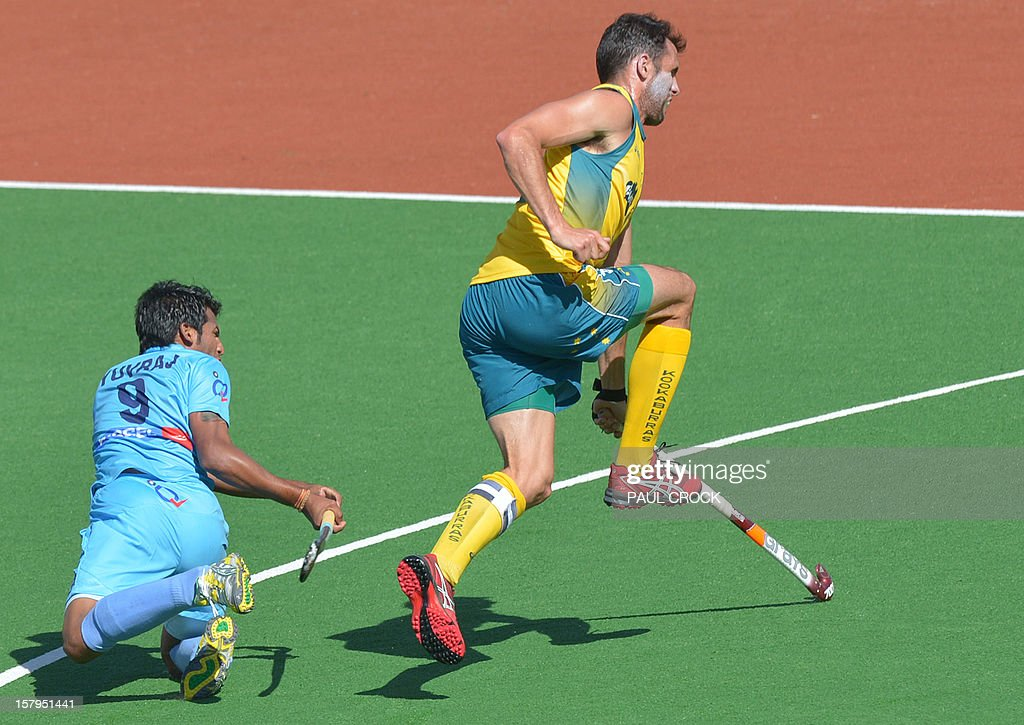 Mark Knowles of Australia (R) leaps as Yuvraj Walmiki of India (L) has a shot at goal during the second semifinal at the men's Hockey Champions Trophy tournament in Melbourne on December 8, 2012. IMAGE STRICTLY RESTRICTED TO EDITORIAL USE - STRICTLY NO COMMERCIAL USE AFP PHOTO / Paul CROCK