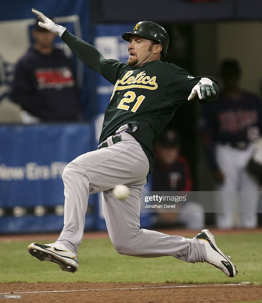 Mark Kotsay of the Oakland Athletics beats the throw to score on a insidethepark home run in the 7th inning against the Minnesota Twins in game two...