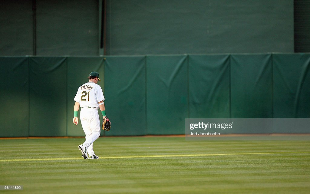 Mark Kotsay #21 of the Oakland Athletics walks in the outfield against the Baltimore Orioles at McAfee Coliseum on August 16, 2005 in Oakland, California.