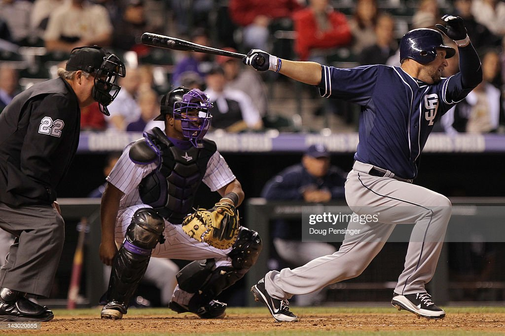 Mark Kotsay of the San Diego Padres singles in the sixth inning as catcher Wilin Rosario of the Colorado Rockies backs up the plate and homeplate...