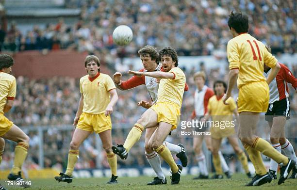 Mark Lawrenson of Liverpool FC clears from Mike Channon of Southampton FC in a Football League Division One match which Liverpool went on to win 32...