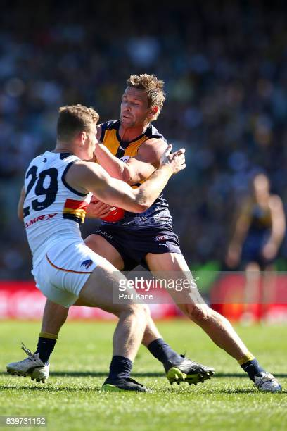 Mark LeCras of the Eagles fends off a tackle by Rory Laird of the Crows during the round 23 AFL match between the West Coast Eagles and the Adelaide...