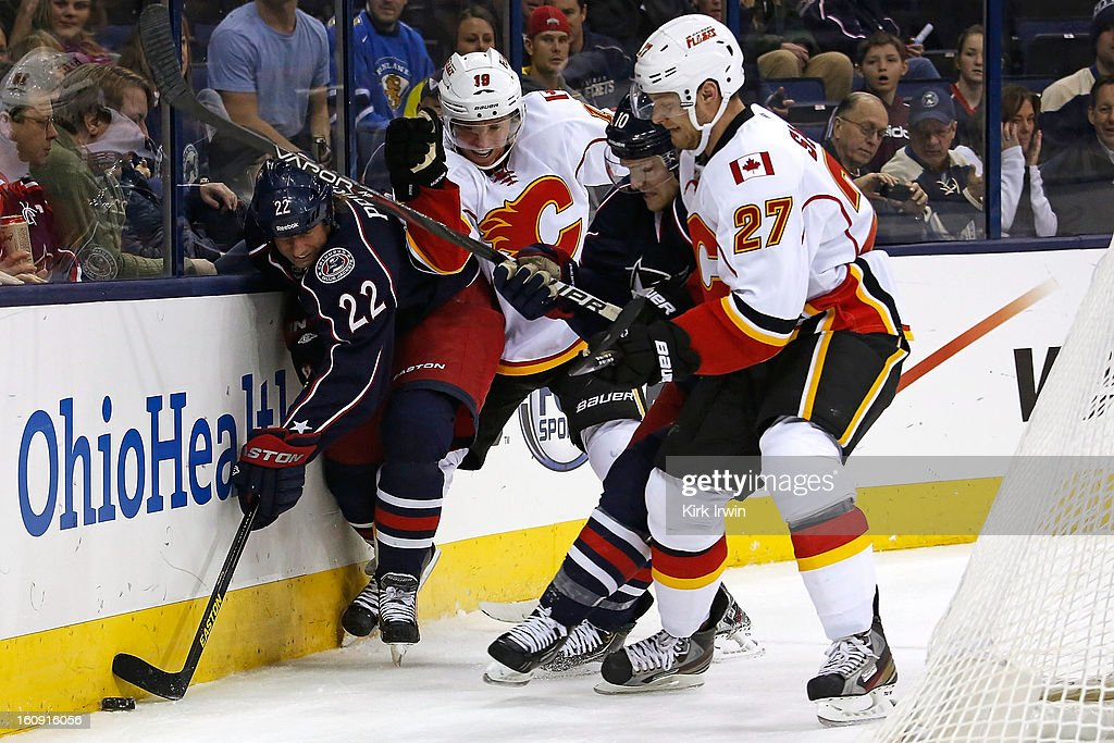 Mark Letestu #10 of the Columbus Blue Jackets attempts to hold off Derek Smith #27 of the Calgary Flames as Vinny Prospal #22 of the Columbus Blue Jackets and Blair Jones #19 of the Calgary Flames battle for control of a loose puck on February 7, 2013 at Nationwide Arena in Columbus, Ohio.