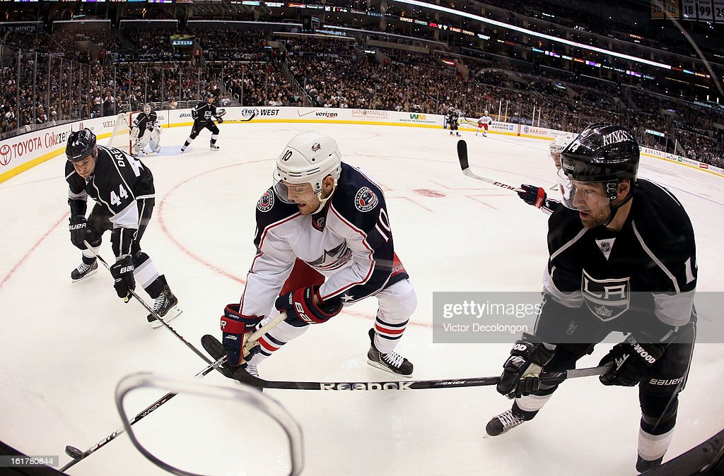 Mark Letestu #10 of the Columbus Blue Jackets vies for the puck in the corner with Davis Drewiske #44 and Justin Williams #14 of the Los Angeles Kings during the NHL game at Staples Center on February 15, 2013 in Los Angeles, California. The Kings defeated the Blue Jackets 2-1.