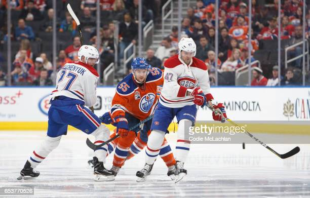 Mark Letestu of the Edmonton Oilers battles against Alex Galchenyuk and Alexander Radulov of the Montreal Canadiens on March 12 2017 at Rogers Place...