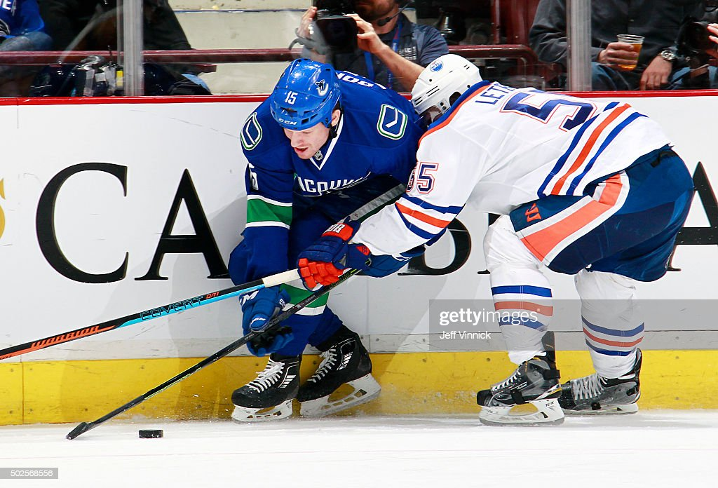 Mark Letestu of the Edmonton Oilers checks Derek Dorsett of the Vancouver Canucks during their NHL game at Rogers Arena December 26 2015 in Vancouver...