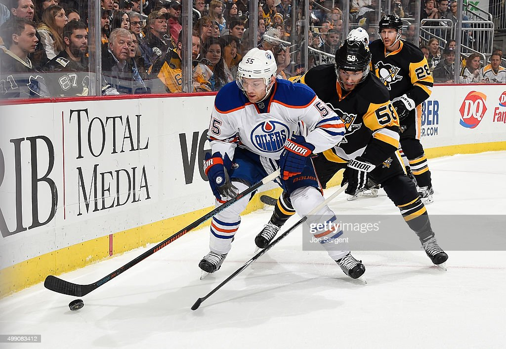 Mark Letestu of the Edmonton Oilers moves the puck in front of Kris Letang of the Pittsburgh Penguins at Consol Energy Center on November 28 2015 in...