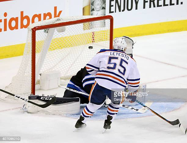 Mark Letestu of the Edmonton Oilers watches as the puck goes over a sprawling Connor Hellebuyck of the Winnipeg Jets for his second goal of the game...