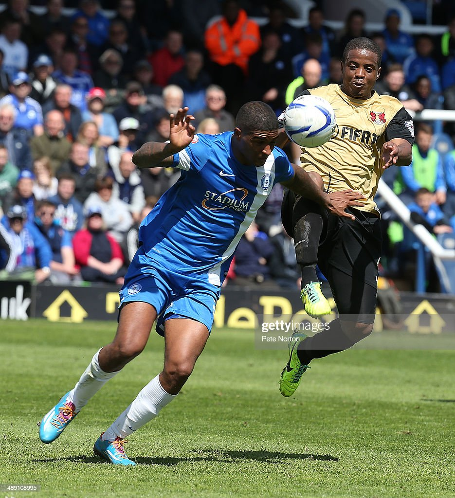 Mark Little of Peterborough United attempts to clear the ball under pressure from <a gi-track='captionPersonalityLinkClicked' href=/galleries/search?phrase=Kevin+Lisbie&family=editorial&specificpeople=226902 ng-click='$event.stopPropagation()'>Kevin Lisbie</a> of Leyton Orient during the Sky Bet League One Semi Final First Leg between Peterborough United and Leyton Orient at London Road Stadium on May 10, 2014 in Peterborough, England.