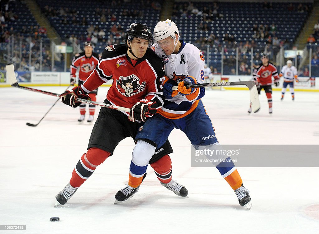Mark Louis #33 of the Portland Pirates checks <a gi-track='captionPersonalityLinkClicked' href=/galleries/search?phrase=Nino+Niederreiter&family=editorial&specificpeople=6667732 ng-click='$event.stopPropagation()'>Nino Niederreiter</a> #22 of the Bridgeport Sound Tigers during an American Hockey League game on January 12, 2013 at the Webster Bank Arena at Harbor Yard in Bridgeport, Connecticut.