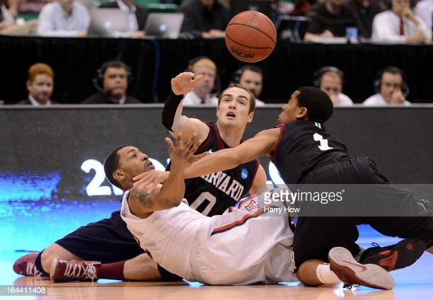 Mark Lyons of the Arizona Wildcats goes after the loose ball with Laurent Rivard and Siyani Chambers of the Harvard Crimson in the first half during...