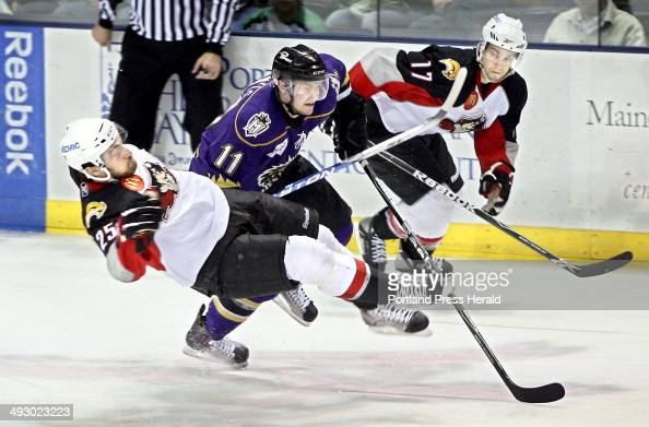 Mark Mancari of the Portland Pirates is upended by Trevor Lewis of the Manchester Monarchs as MarcAndre Gragnani of the Pirates looks on during their...