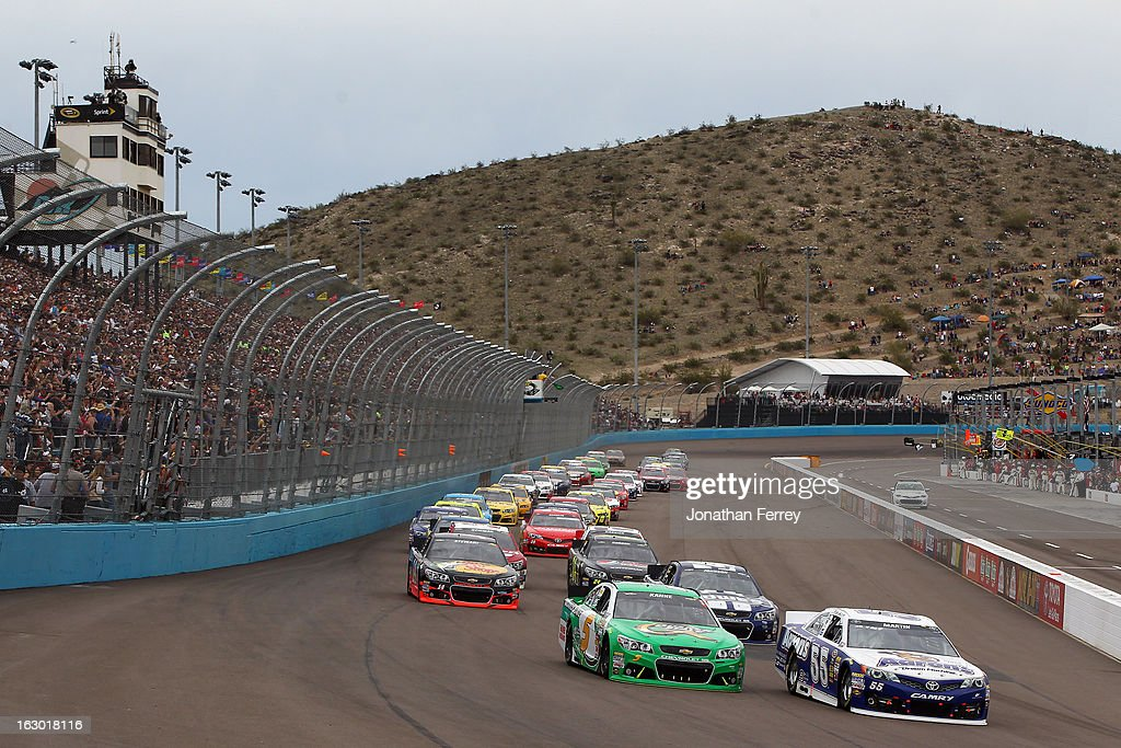 Mark Martin driver of the Aaron's Dream Machine Toyota and Kasey Kahne driver of the Quaker State Chevrolet lead the first lap during the NASCAR...