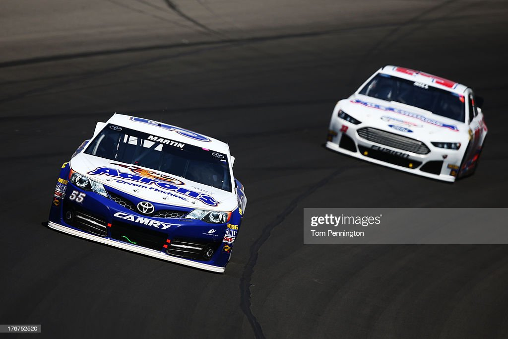 Mark Martin, driver of the #55 Aaron's Dream Machine Toyota, leads Timmy Hill, driver of the #32 U.S. Chrome Ford, during the NASCAR Sprint Cup Series 44th Annual Pure Michigan 400 at Michigan International Speedway on August 18, 2013 in Brooklyn, Michigan.