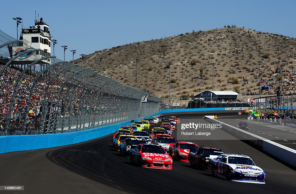Mark Martin driver of the Aaron's Toyota leads the first lap of the NASCAR Sprint Cup Series SUBWAY Fresh Fit 500 at Phoenix International Raceway on...