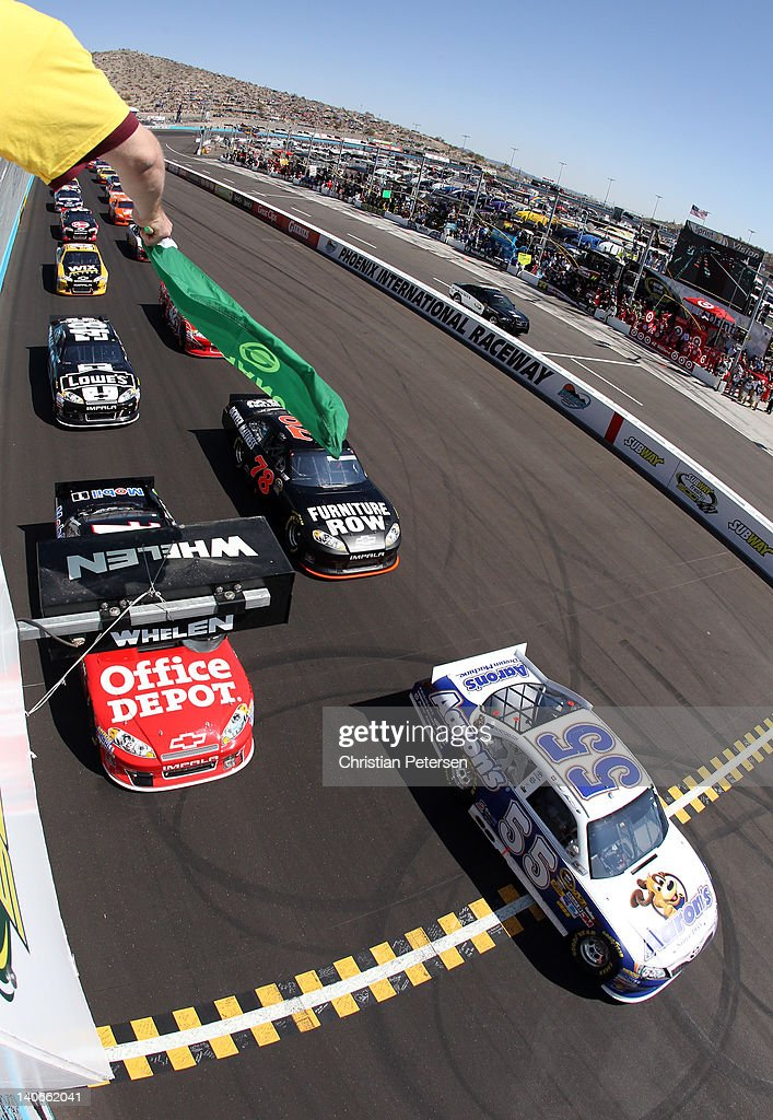 Mark Martin driver of the Aaron's Toyota takes the green flag to start the NASCAR Sprint Cup Series SUBWAY Fresh Fit 500 at Phoenix International...