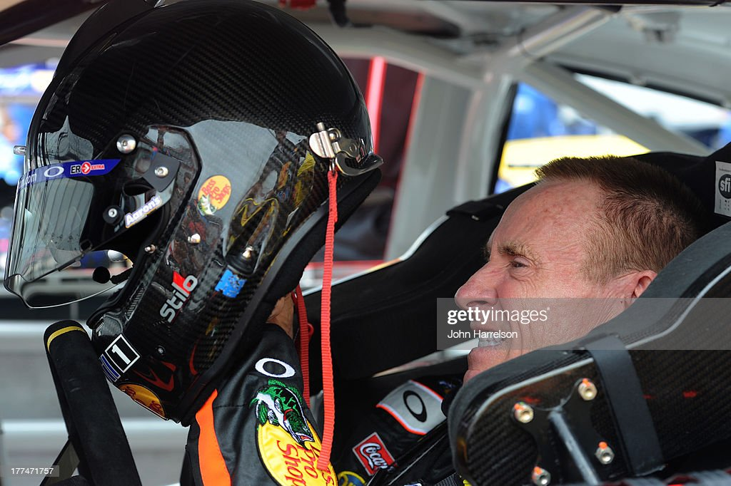 Mark Martin, driver of the #14 Bass Pro Shops / Mobil 1 Chevrolet, adjusts his helmet in his car during practice for the NASCAR Sprint Cup Series IRWIN Tools Night Race at Bristol Motor Speedway on August 23, 2013 in Bristol, Tennessee.