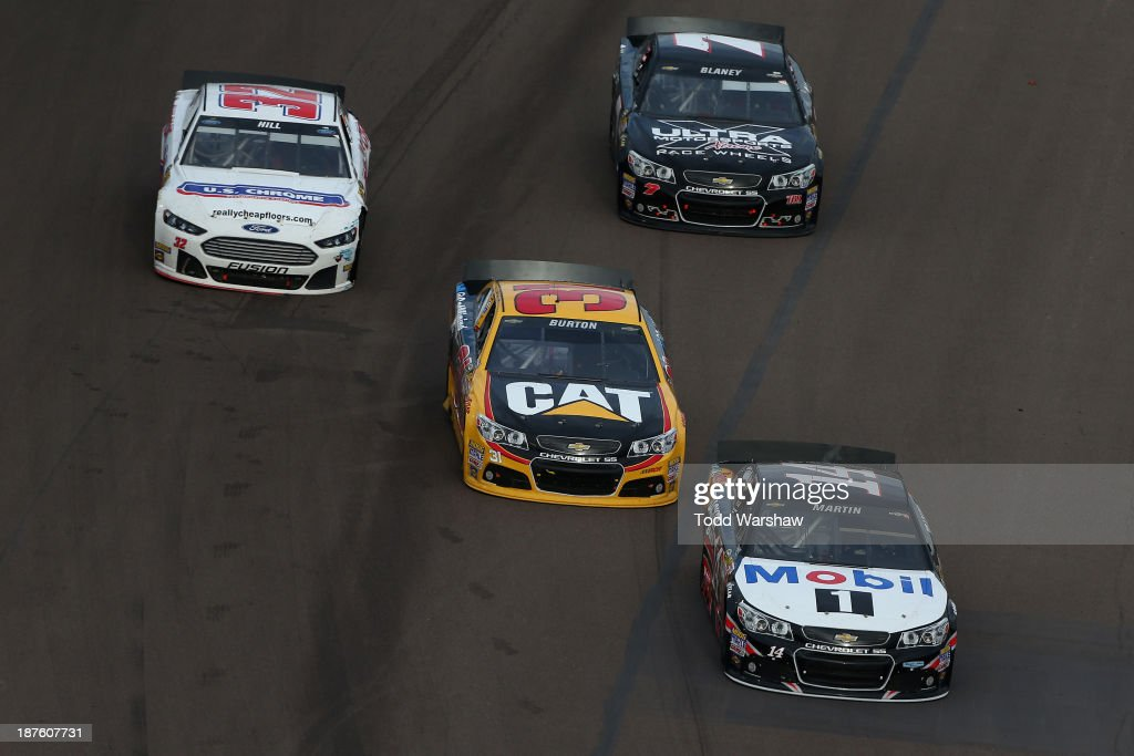 Mark Martin, driver of the #14 Bass Pro Shops / Mobil 1 Chevrolet, leads Jeff Burton, driver of the #31 Caterpillar Chevrolet, Timmy Hill, driver of the #32 U.S. Chrome Ford, and Dave Blaney, driver of the #7 Ultra Wheel Chevrolet, during the NASCAR Sprint Cup Series AdvoCare 500 at Phoenix International Raceway on November 10, 2013 in Avondale, Arizona.