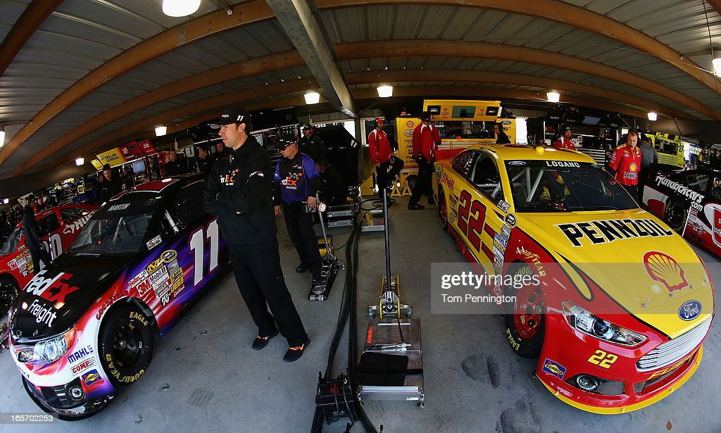 Mark Martin, driver of the #11 FedEx Freight Toyota, and Joey Logano, driver of the #22 Shell Pennzoil Ford, prepare for practice for the NASCAR Sprint Cup Series STP Gas Booster 500 on April 5, 2013 at Martinsville Speedway in Ridgeway, Virginia.
