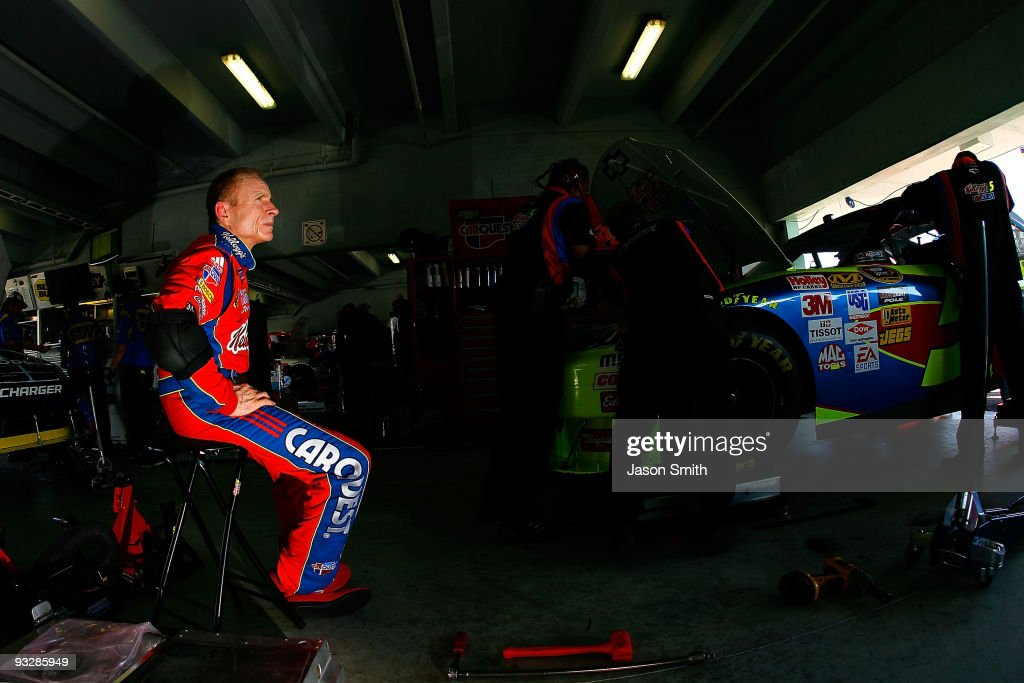 <a gi-track='captionPersonalityLinkClicked' href=/galleries/search?phrase=Mark+Martin&family=editorial&specificpeople=204455 ng-click='$event.stopPropagation()'>Mark Martin</a> (L), driver of the #5 Kellogg's/CARQUEST Chevrolet, sits in the garage as crew members work on his car in the garage during practice for the NASCAR Sprint Cup Series Ford 400 at Homestead-Miami Speedway on November 21, 2009 in Homestead, Florida.