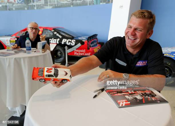 Mark Martin NASCAR Hall of Famer speaks to Clint Bowyer driver of the Ford Fusion for StewartHaas Racing as they sign autographs for fans during the...