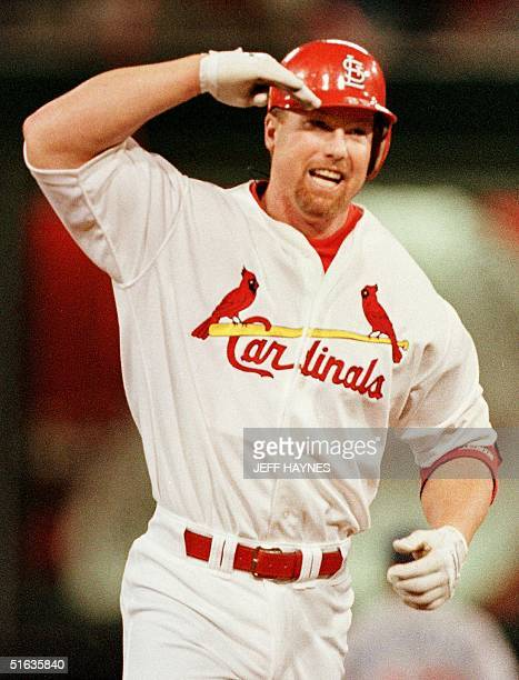 Mark McGwire of the St Louis Cardinals salutes his father after hitting his 62nd homerun 08 September at Busch Stadium in St Louis MO McGwire broke...