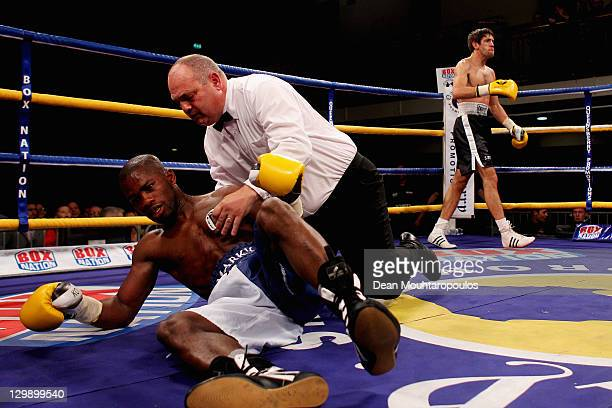 Mark McKray of Tottenham is helped by the referee after being knocked out by Danny Davis of Croydon during their LightWelterweight Contest held at...
