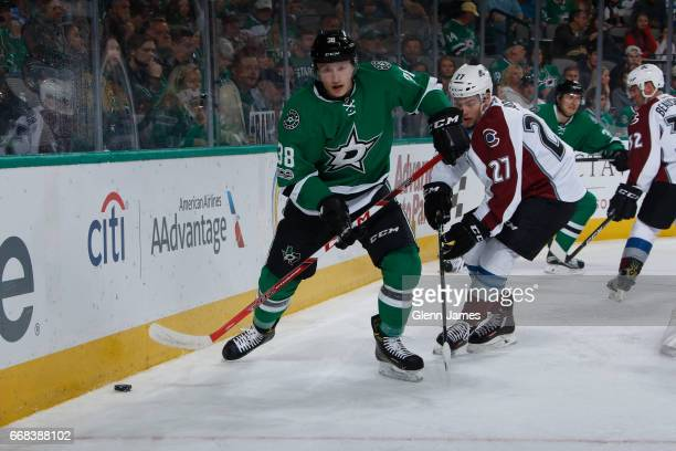 Mark McNeill of the Dallas Stars tries to keep the puck away against Tyson Jost of the Colorado Avalanche at the American Airlines Center on April 8...