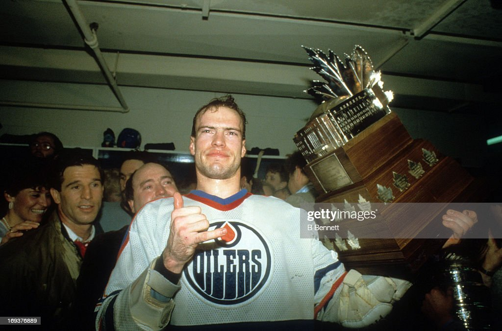 Mark Messier #11 of the Edmonton Oilers celebrates in the locker room with the Conn Smyth Trophy after the Oilers defeated the New York Islanders in Game 5 of the 1984 Stanley Cup Finals on May 19, 1984 at the Northlands Coliseum in Edmonton, Alberta, Canada.