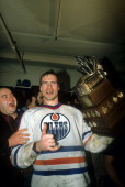 Mark Messier of the Edmonton Oilers celebrates in the locker room with the Conn Smyth Trophy after the Oilers defeated the New York Islanders in Game...
