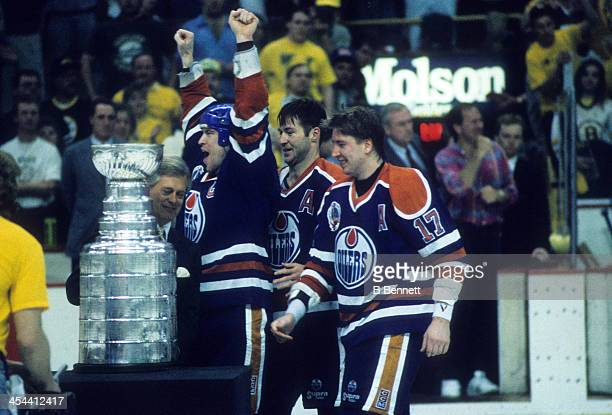 Mark Messier of the Edmonton Oilers celebrates with teammates Kevin Lowe and Jari Kurri after Game 5 of the 1990 Stanley Cup Finals against the...