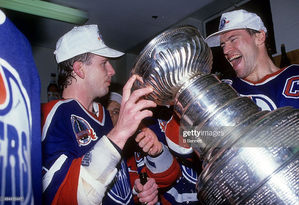 Mark Messier #11 of the Edmonton Oilers helps out teammate Joe Murphy drink from the Stanley Cup in the locker room as they celebrate after Game 5 of the 1990 Stanley Cup Finals against the Boston Bruins on May 24, 1990 at the Boston Garden in Boston, Massachusetts. The Oilers defeated the Bruins 4-1 and won the Series 4 games to 1.