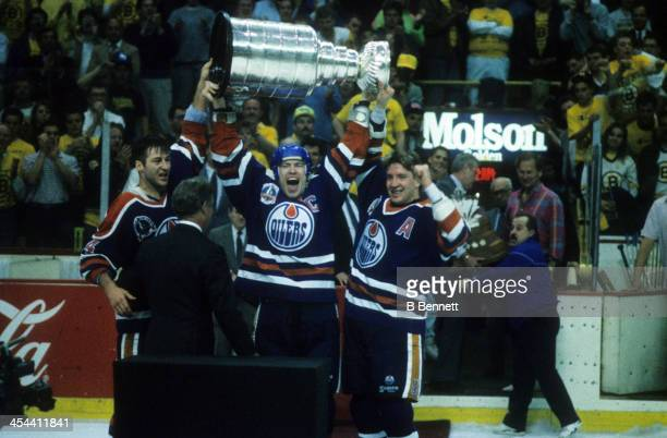 Mark Messier of the Edmonton Oilers hoists the Stanley Cup over his head and shouts as he and teammates Kevin Lowe and Jari Kurri celebrate after...
