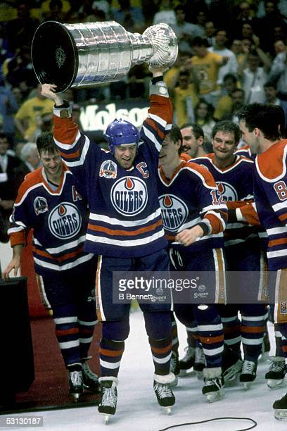 Mark Messier of the Edmonton Oilers hoists the Stanley Cup over his head as his teammates celebrate their Game 5 win over the Boston Bruins on May 24...