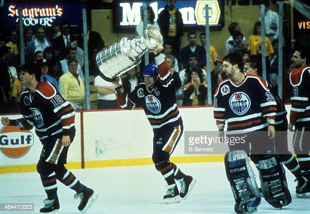 Mark Messier of the Edmonton Oilers hoists the Stanley Cup Trophy over his head as his teammates Craig Simpson and goalie Bill Ranford celebrate...