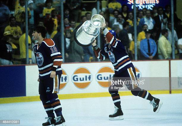 Mark Messier of the Edmonton Oilers hoists the Stanley Cup Trophy over his head as his teammate Craig Simpson celebrates after Game 5 of the 1990...