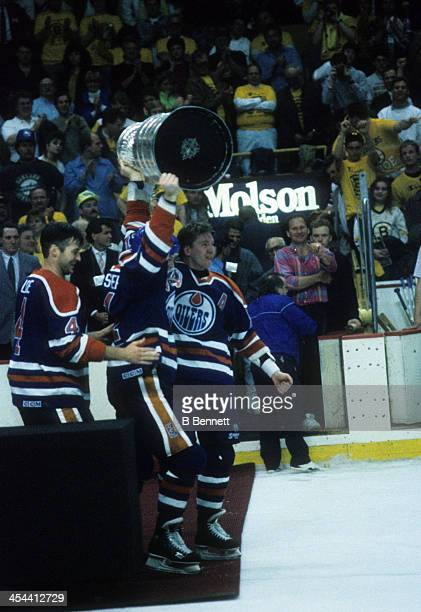 Mark Messier of the Edmonton Oilers hoists the Stanley Cup Trophy over his head as his teammates celebrate after Game 5 of the 1990 Stanley Cup...