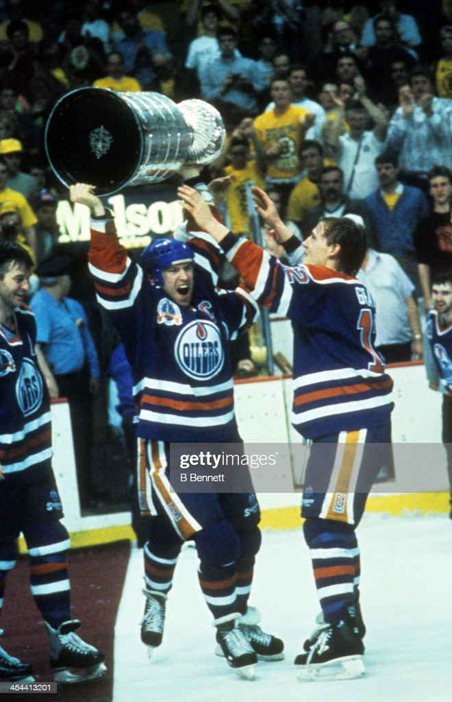 Mark Messier #11 of the Edmonton Oilers hoists the Stanley Cup Trophy over his head as his teammates celebrate after Game 5 of the 1990 Stanley Cup Finals against the Boston Bruins on May 24, 1990 at the Boston Garden, Boston, Massachusetts. The Oilers defeated the Bruins 4-1 and won the Series 4 games to 1.