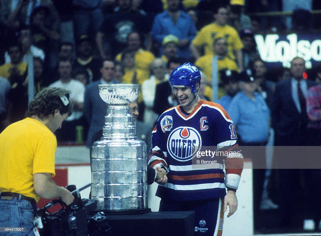Mark Messier #11 of the Edmonton Oilers is presented the Stanley Cup Trophy after Game 5 of the 1990 Stanley Cup Finals against the Boston Bruins on May 24, 1990 at the Boston Garden in Boston, Massachusetts.