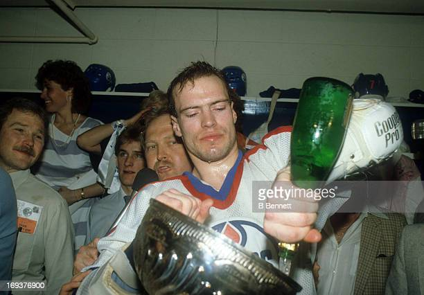 Mark Messier of the Edmonton Oilers pours champagne into the Stanley Cup Trophy while celebrating in the locker room after the Oilers defeated the...