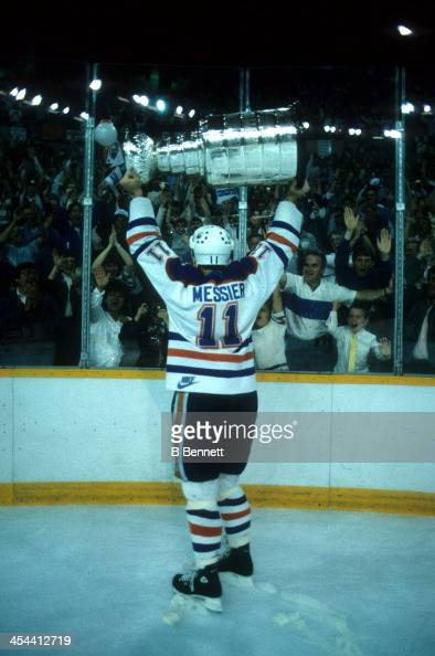 Mark Messier of the Edmonton Oilers skates around the rink celebrating with the crowd while holding the Stanley Cup Trophy after Game 7 of the 1987...