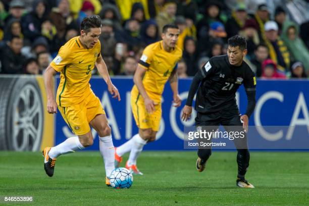Mark Milligan of the Australian National Football Team runs with the ball in front of Pokklaw Anan of the Thailand National Football Team during the...