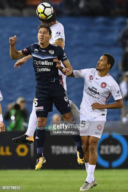 Mark Milligan of the Victory and Brendan Hamill of the Wanderers compete to head the ball during the round five ALeague match between the Melbourne...