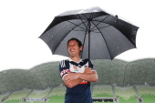 Mark Milligan of the Victory takes cover from the rain with an umbrella during an ALeague 1000th match media session at AAMI Park on December 4 2013...