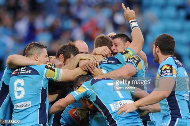 Mark Minichiello of the Titans celebrates victory with team mates after extra time during the round 26 NRL match between the Gold Coast Titans and...