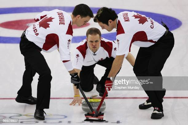 Mark Nichols of Canada releases a stone as Brad Gushue and Jamie Korab of Canada brush the ice during the Gold medal match of the men's curling...