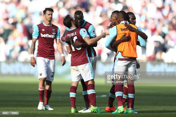 Mark Noble of West Ham United and Cheikhou Kouyate of West Ham Unitwins a header embrace after the Premier League match between West Ham United and...