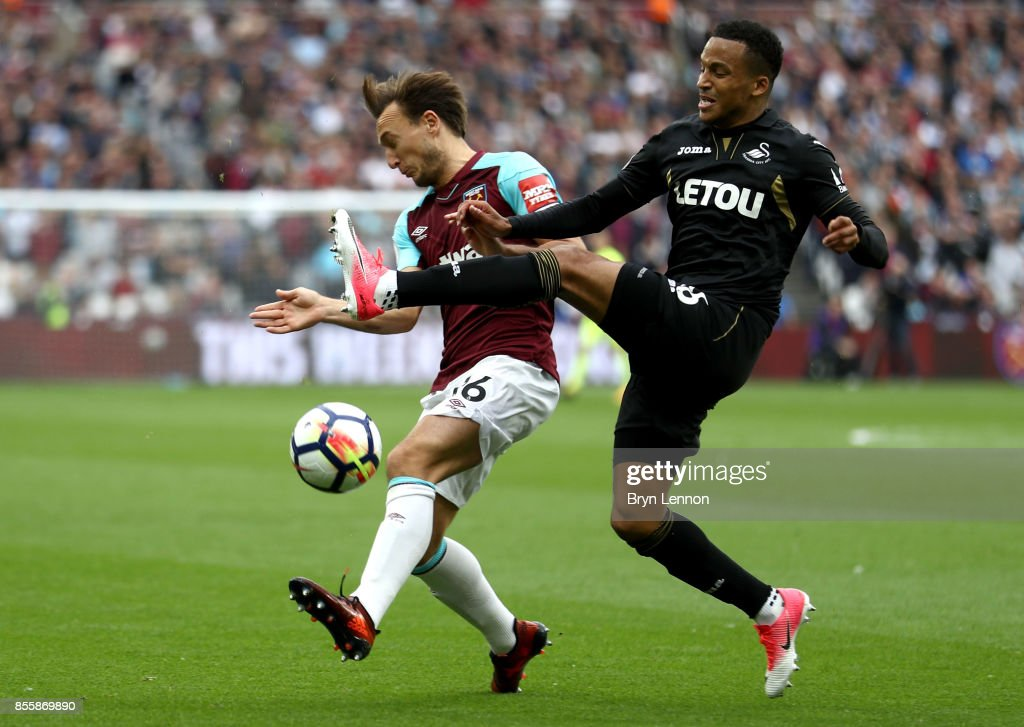 Mark Noble of West Ham United and Martin Olsson of Swansea City battle for possession during the Premier League match between West Ham United and Swansea City at London Stadium on September 30, 2017 in London, England.