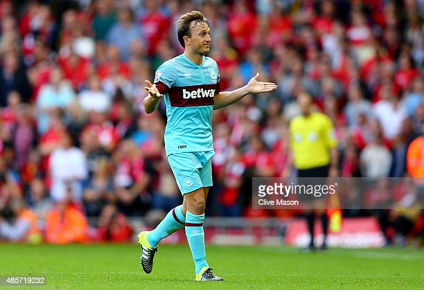 Mark Noble of West Ham United approaches to the fourth official questioning his red card during the Barclays Premier League match between Liverpool...