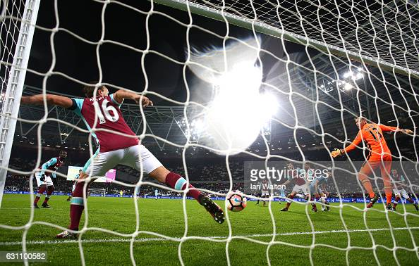 Mark Noble of West Ham United attempts to stop as John Stones of Manchester City scores his sides fifth goal during The Emirates FA Cup Third Round...